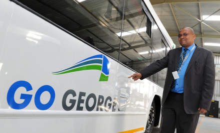 Executive Mayor of George, Alderman Charles Standers shows of the GO GEORGE logo on one of the completed buses at the Busmark plant in Johannesburg.