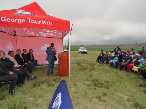 Minister Madikizela addresses the beneficiaries of the new structures with delegates looking on