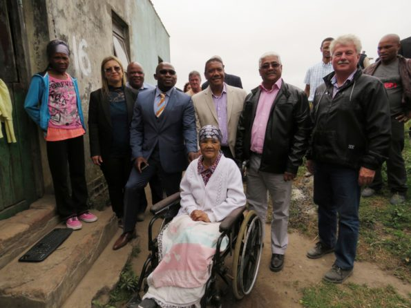 One of the Beneficiaries, Katriena Malan (70) in a wheelchair with the role players at the back. Second from left is the Honourable Minister of Human Settlements, Bonginkozi Madikizela flanked to left by Athena Makan, Middle Manager Key Customer Accounts Western and Northern Cape: Eskom. To his right are Executive Mayor of George, Ald Melvin Naik, Cllr Edmund Bussack, Portfolio Councillor for Rural Development and Nelius van Greunen from Van Greunen Boerdery